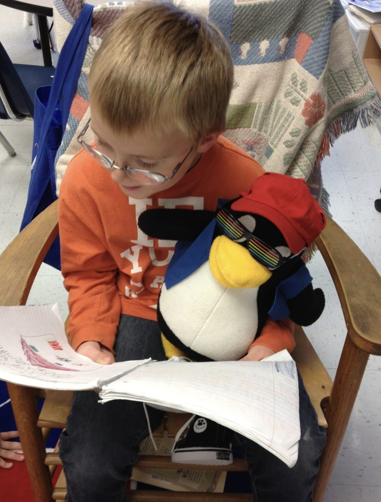first grade boy reading a journal entry